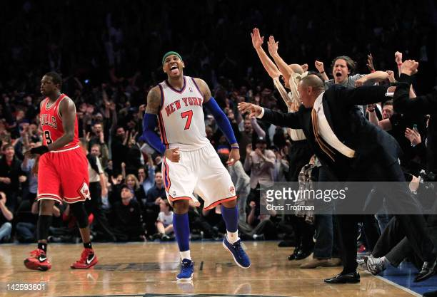 Carmelo Anthony of the New York Knicks celebrates his game winning three pointer against as Luol Deng of the Chicago Bulls looks on at Madison Square...