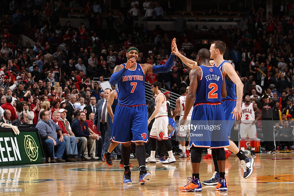 Carmelo Anthony #7 of the New York Knicks celebrates with teammates Steve Novak #16 and Raymond Felton #2 during the game against the Chicago Bulls on April 11, 2013 at the United Center in Chicago, Illinois.