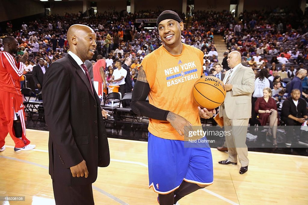Carmelo Anthony #7 of the New York Knicks chats with fellow Baltimore native Sam Cassell, assistant coach of the Washington Wizards during the pre-season game at the Baltimore Arena on October 17, 2013 in Baltimore, MD.
