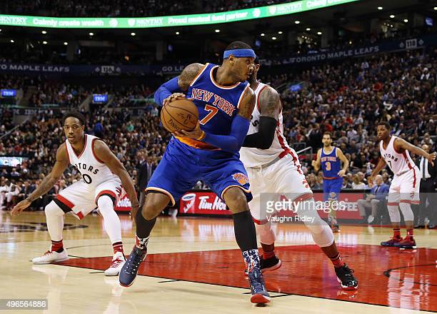 Carmelo Anthony of the New York Knicks dribbles past James Johnson of the Toronto Raptors during an NBA game at the Air Canada Centre on November 10...