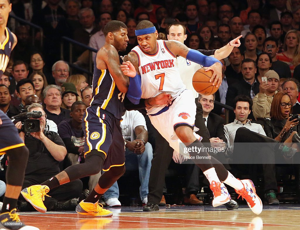 Carmelo Anthony #7 of the New York Knicks dribbles the ball around Paul George #24 of the Indiana Pacers at Madison Square Garden on November 20, 2013 in New York City.