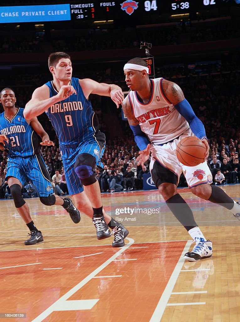 Carmelo Anthony #7 of the New York Knicks drives against Nikola Vucevic #9 of the Orlando Magic on January 30, 2013 at Madison Square Garden in New York City.