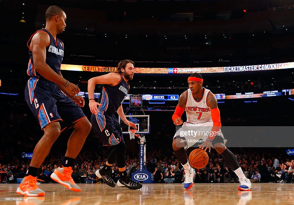Carmelo Anthony #7 of the New York Knicks drives against Ramon Sessions #7 and Josh McRoberts #11 of the Charlotte Bobcats in the first half at Madison Square Garden on Friday, October 25 2013 in New York City. The Bobcats defeated the Knicks 85-83.