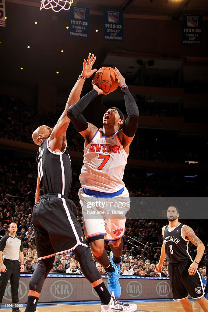 Carmelo Anthony #7 of the New York Knicks drives to the basket against Keith Bogans #10 of the Brooklyn Nets on January 21, 2013 at Madison Square Garden in New York City.