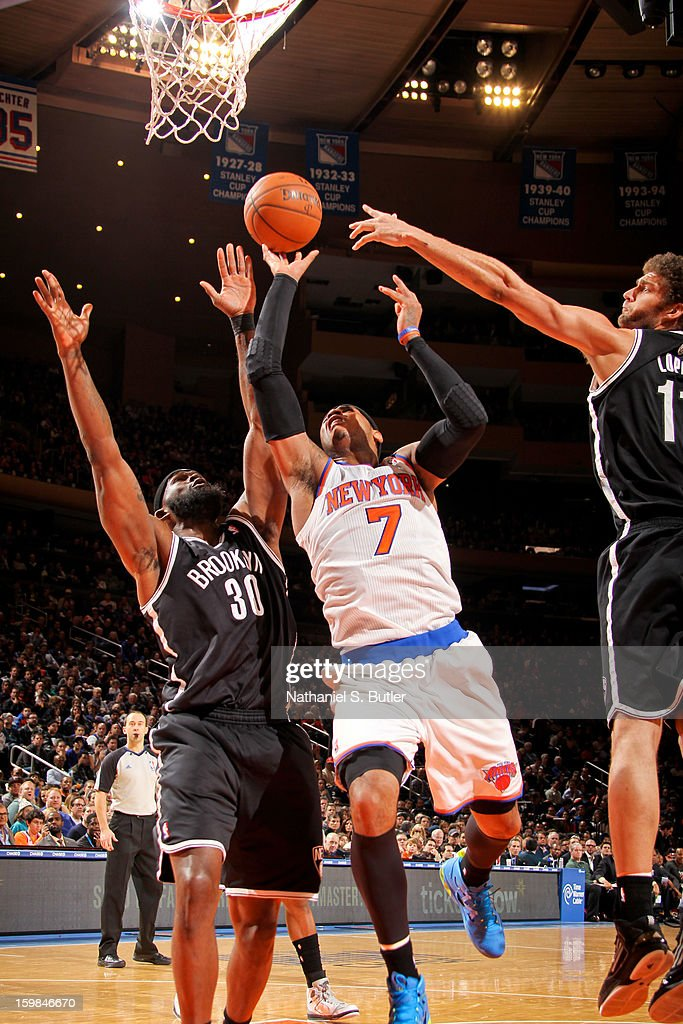 Carmelo Anthony #7 of the New York Knicks drives to the basket against Reggie Evans #30 and Brook Lopez #11 of the Brooklyn Nets on January 21, 2013 at Madison Square Garden in New York City.