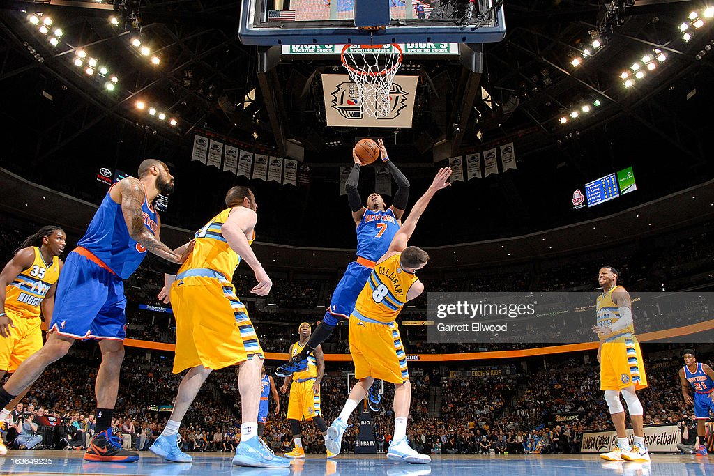 Carmelo Anthony #7 of the New York Knicks drives to the basket against Danilo Gallinari #8 of the Denver Nuggets on March 13, 2013 at the Pepsi Center in Denver, Colorado.