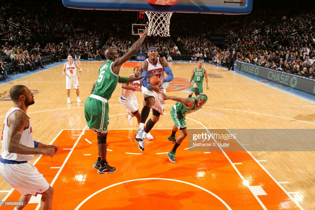 Carmelo Anthony #7 of the New York Knicks goes to the basket against Kevin Garnett #5 and Paul Pierce #34 of the Boston Celtics on January 7, 2013 at Madison Square Garden in New York City.