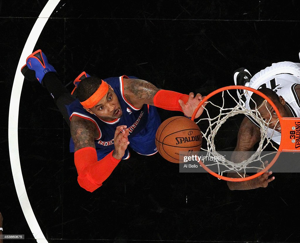 Carmelo Anthony #7 of the New York Knicks grabs a rebound against the Brooklyn Nets during their game at the Barclays Center on December 5, 2013 in the Brooklyn borough of New York City.