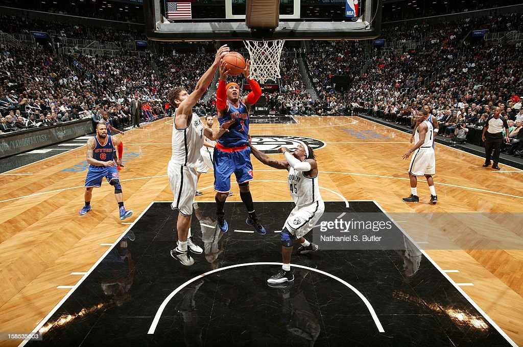 <a gi-track='captionPersonalityLinkClicked' href=/galleries/search?phrase=Carmelo+Anthony&family=editorial&specificpeople=201494 ng-click='$event.stopPropagation()'>Carmelo Anthony</a> #7 of the New York Knicks grabs a rebound over <a gi-track='captionPersonalityLinkClicked' href=/galleries/search?phrase=Brook+Lopez&family=editorial&specificpeople=3847328 ng-click='$event.stopPropagation()'>Brook Lopez</a> #11 of the Brooklyn Nets on November 26, 2012 at the Barclays Center in the Brooklyn Borough of New York City.