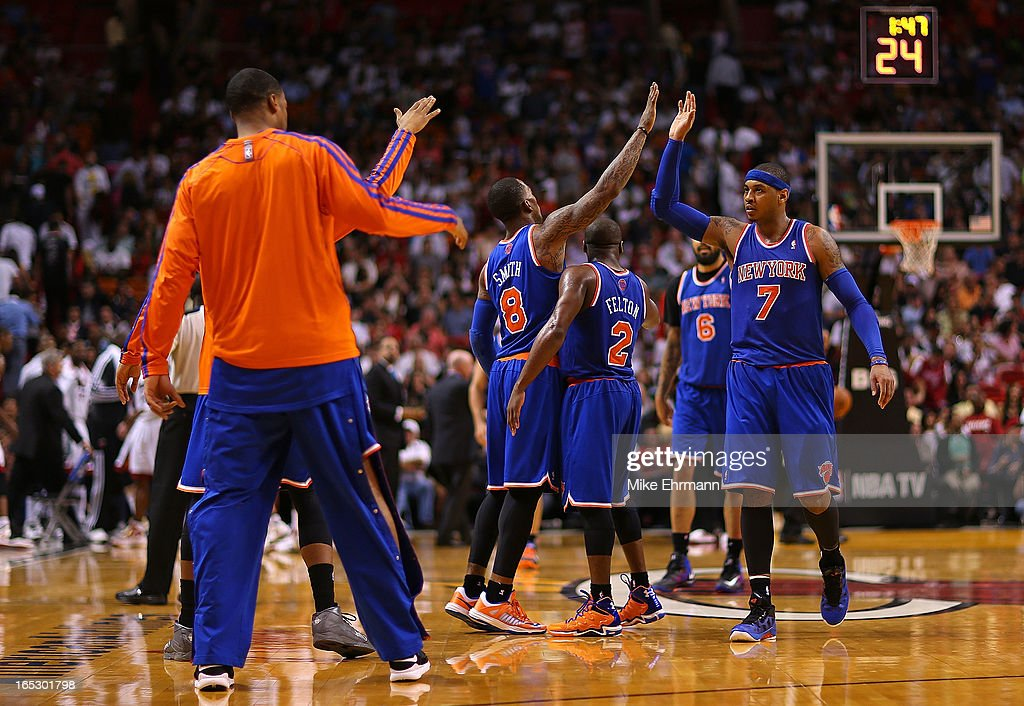 Carmelo Anthony #7 of the New York Knicks high fives teammates during a game against the Miami Heat at American Airlines Arena on April 2, 2013 in Miami, Florida.