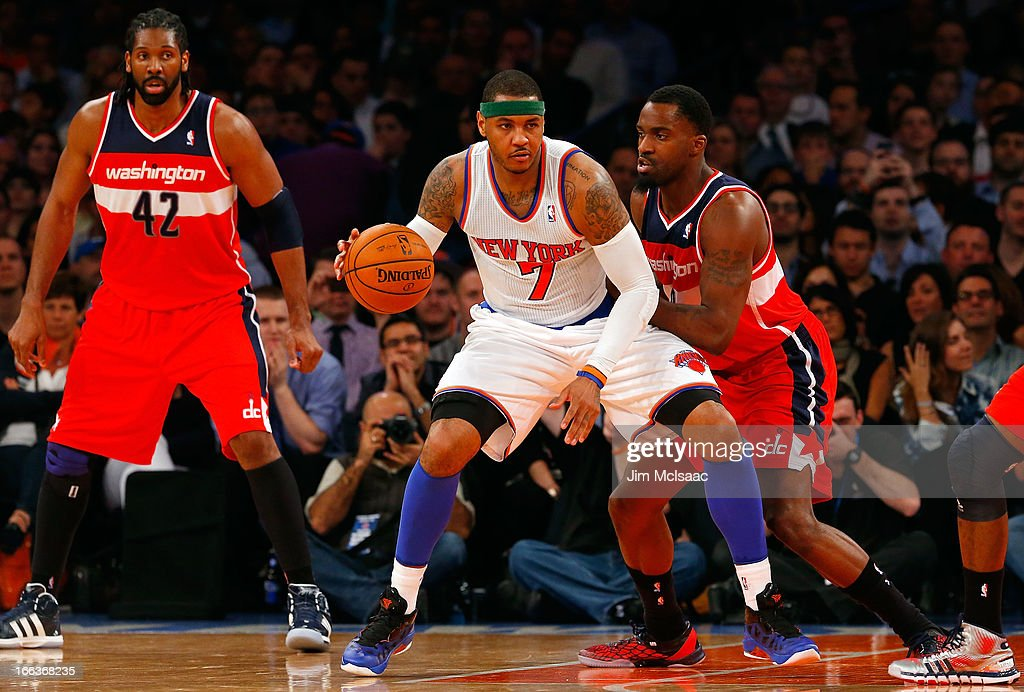 Carmelo Anthony #7 of the New York Knicks in action against Martell Webster #9 and Nenê #42 of the Washington Wizards at Madison Square Garden on April 9, 2013 in New York City. The Knicks defeated the Wizards 120-99.