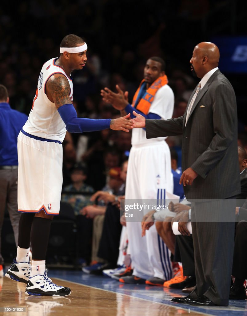 Carmelo Anthony #7 of the New York Knicks is congratulated by head coach Mike Woodson after Anthony was pulled from the game against the Orlando Magic on January 30, 2013 at Madison Square Garden in New York City. This marked Anthony's 30th twenty point game.The New York Knicks defeated the Orlando Magic 113-97.