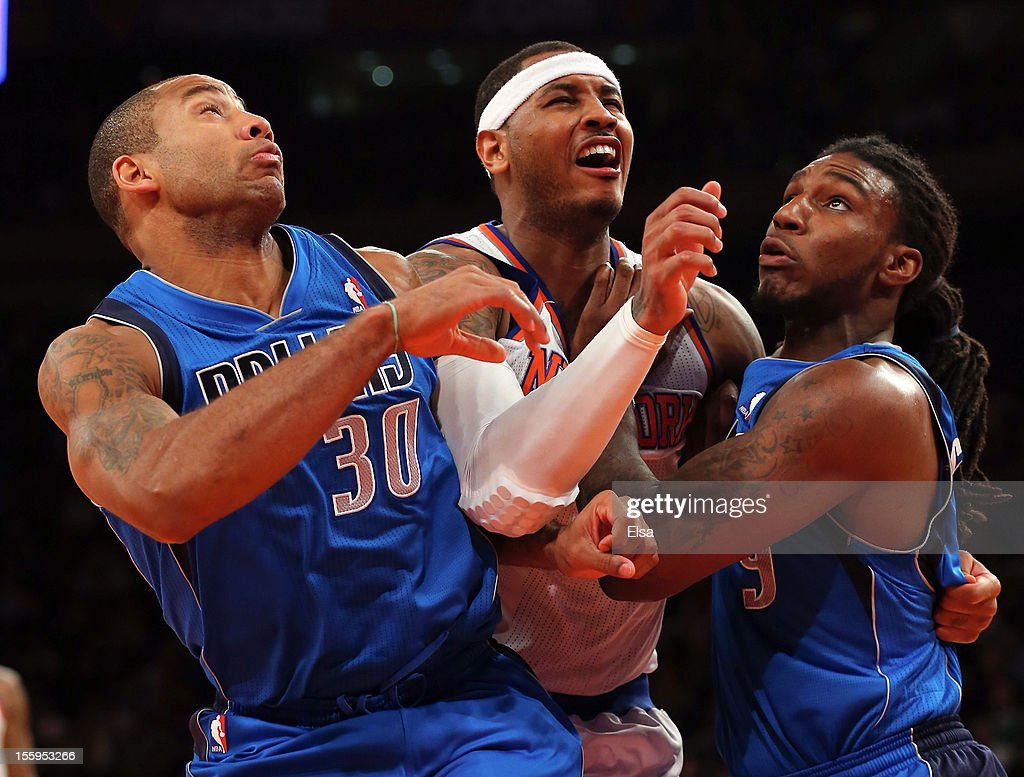 Carmelo Anthony #7 of the New York Knicks is sandwiched between Dahntay Jones #30 and Jae Crowder #9 of the Dallas Mavericks on November 9, 2012 at Madison Square Garden in New York City.The New York Knicks defeated the Dallas Mavericks 104-94.