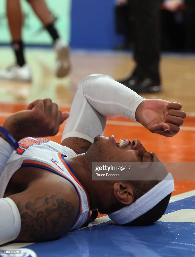 Carmelo Anthony #7 of the New York Knicks lies on the court after being fouled in the game against the Los Angeles Lakers at Madison Square Garden on December 13, 2012 in New York City. Anthony left the game with a sprained ankle.