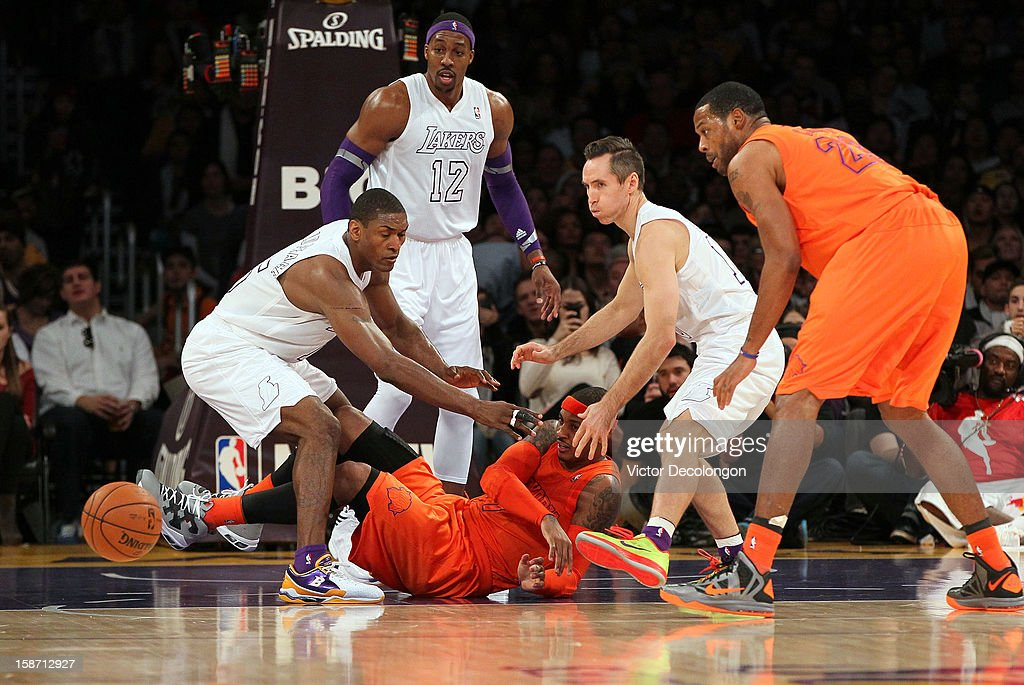 Carmelo Anthony #7 of the New York Knicks makes a pass from the floor as Metta World Peace #15 and Steve Nash #10 of the Los Angeles Lakers try to defend the play during the NBA game at Staples Center on December 25, 2012 in Los Angeles, California.
