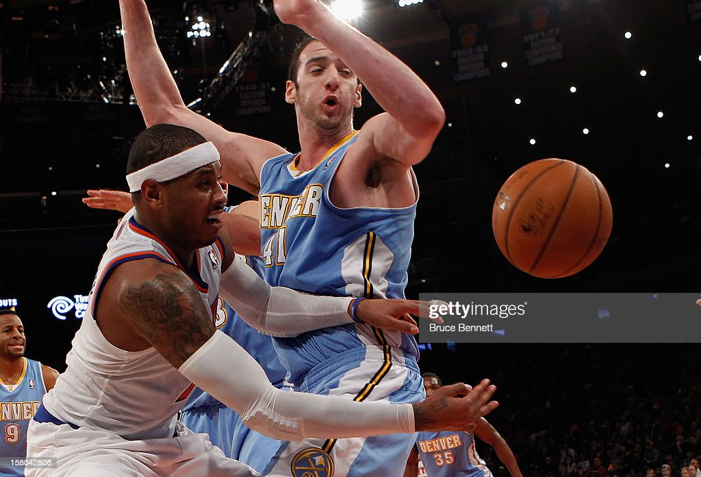 Carmelo Anthony #7 of the New York Knicks passes the ball around Kosta Koufos #41 of the Denver Nuggets at Madison Square Garden on December 9, 2012 in New York City.