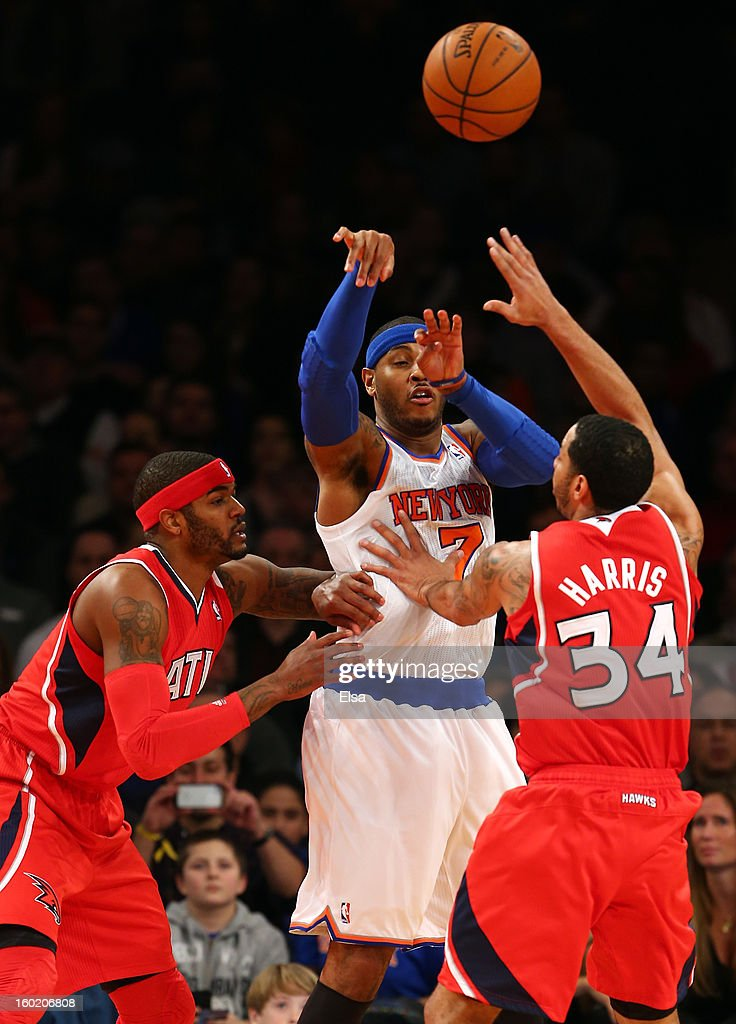 Carmelo Anthony #7 of the New York Knicks passes the ball under pressure from Josh Smith #5 and Devin Harris #34 of the Atlanta Hawks on January 27, 2013 at Madison Square Garden in New York City.