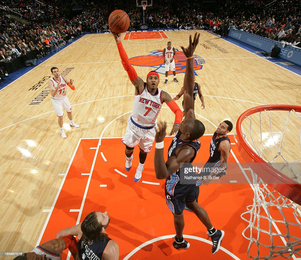 <a gi-track='captionPersonalityLinkClicked' href=/galleries/search?phrase=Carmelo+Anthony&family=editorial&specificpeople=201494 ng-click='$event.stopPropagation()'>Carmelo Anthony</a> #7 of the New York Knicks shoots against <a gi-track='captionPersonalityLinkClicked' href=/galleries/search?phrase=Bismack+Biyombo&family=editorial&specificpeople=7640443 ng-click='$event.stopPropagation()'>Bismack Biyombo</a> #0 of the Charlotte Bobcats during a preseason game on October 25, 2013 at Madison Square Garden in New York City.