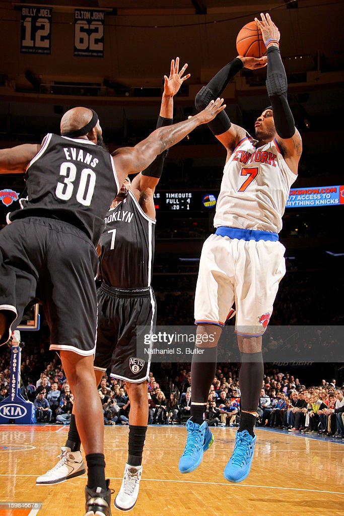 Carmelo Anthony #7 of the New York Knicks shoots against Reggie Evans #30 and Joe Johnson #7 of the Brooklyn Nets on January 21, 2013 at Madison Square Garden in New York City.