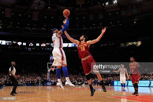 Carmelo Anthony of the New York Knicks shoots the ball over Omri Casspi of the Cleveland Cavaliers at Madison Square Garden on February 29 2012 in...