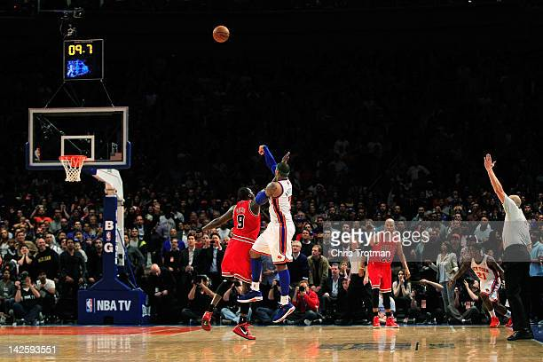 Carmelo Anthony of the New York Knicks shoots the game winning three pointer over Luol Deng of the Chicago Bulls at Madison Square Garden on April 8...