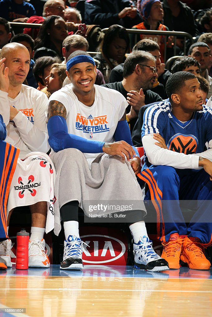 Carmelo Anthony #7 of the New York Knicks smiles on the bench during the game against the San Antonio Spurs on January 3, 2013 at Madison Square Garden in New York City.