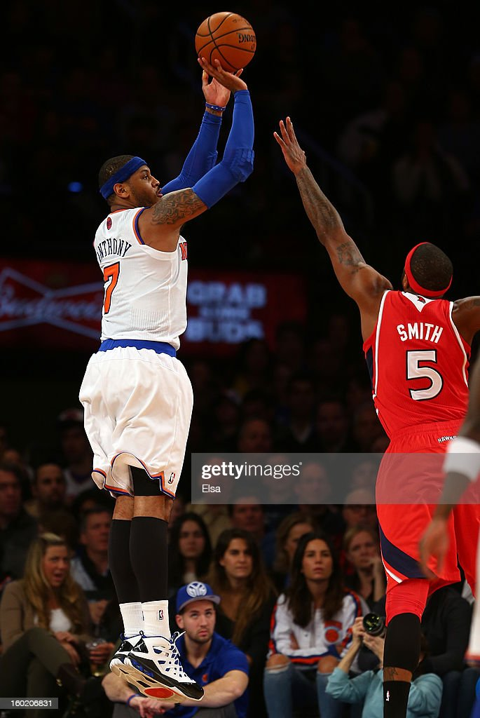 Carmelo Anthony #7 of the New York Knicks takes a shot as Josh Smith #5 of the Atlanta Hawks defends on January 27, 2013 at Madison Square Garden in New York City.