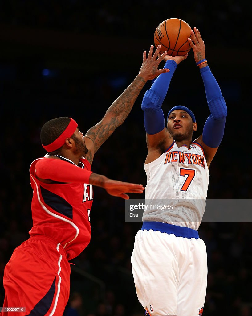 Carmelo Anthony #7 of the New York Knicks takes a shot as Josh Smith #5 of the Atlanta Hawks defends on January 27, 2013 at Madison Square Garden in New York City. The New York Knicks defeated the Atlanta Hawks 106-104.