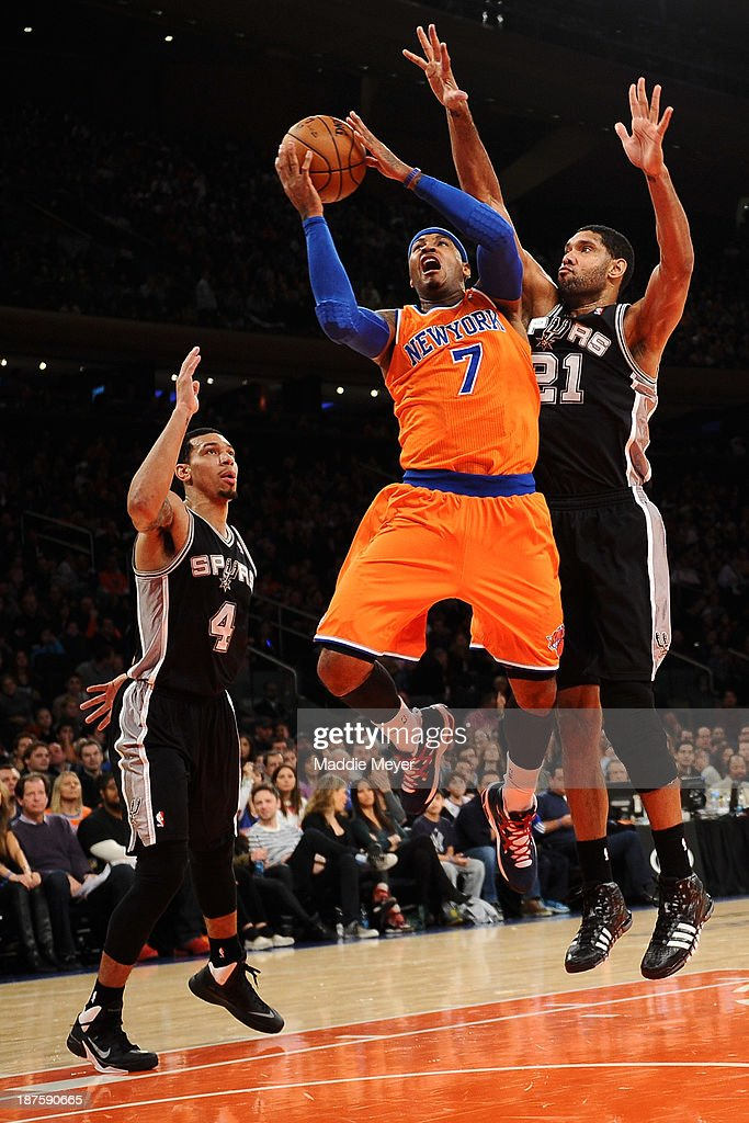 <a gi-track='captionPersonalityLinkClicked' href=/galleries/search?phrase=Carmelo+Anthony&family=editorial&specificpeople=201494 ng-click='$event.stopPropagation()'>Carmelo Anthony</a> #7 of the New York Knicks takes a shot between <a gi-track='captionPersonalityLinkClicked' href=/galleries/search?phrase=Tim+Duncan&family=editorial&specificpeople=201467 ng-click='$event.stopPropagation()'>Tim Duncan</a> #21 of the San Antonio Spurs and Danny Green #4 of the San Antonio Spurs during the second half at Madison Square Garden on November 10, 2013 in New York City. The Spurs defeat the Knicks 120-89.