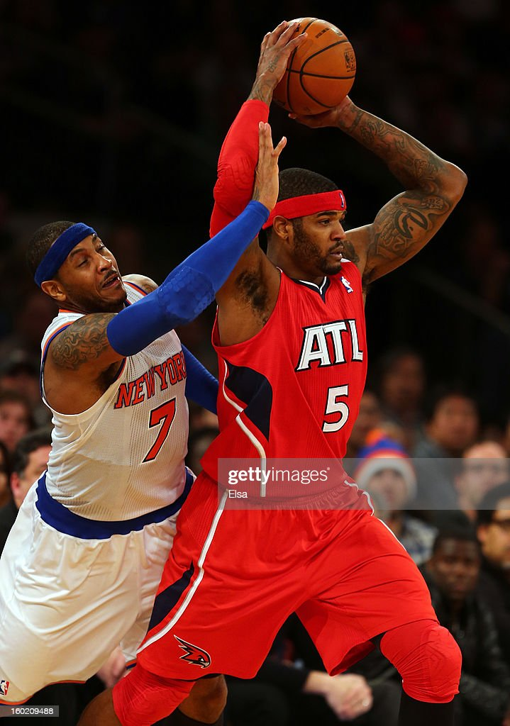 Carmelo Anthony #7 of the New York Knicks tries to get the ball from Josh Smith #5 of the Atlanta Hawks on January 27, 2013 at Madison Square Garden in New York City. The New York Knicks defeated the Atlanta Hawks 106-104.