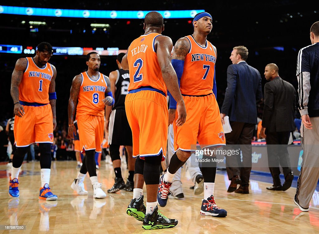 Carmelo Anthony #7 of the New York Knicks walks into the locker room during half time against the San Antonio Spurs with his teammates Raymond Felton #2, J.R. Smith #8 and Amar'e Stoudemire #1 at Madison Square Garden on November 10, 2013 in New York City. The Spurs defeat the Knicks 120-89.