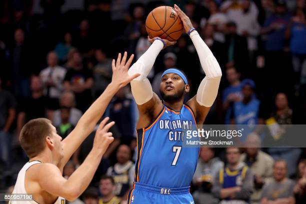 Carmelo Anthony of the Oklahoma City Thunder puts up a shot over Nikola Jokic of the Denver Nuggets at the Pepsi Center on October 10 2017 in Denver...