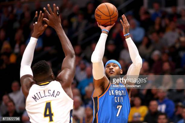 Carmelo Anthony of the Oklahoma City Thunder puts up a shot over Paul Millsap of the Denver Nuggets at the Pepsi Center on November 9 2017 in Denver...