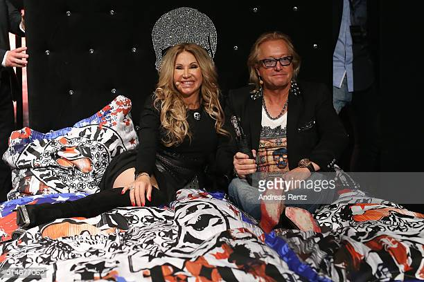 Carmen and Robert Geiss sitting on a bed during the public launch of a new fragrance 'Roberto Geissini' on March 10 2016 in Cologne Germany