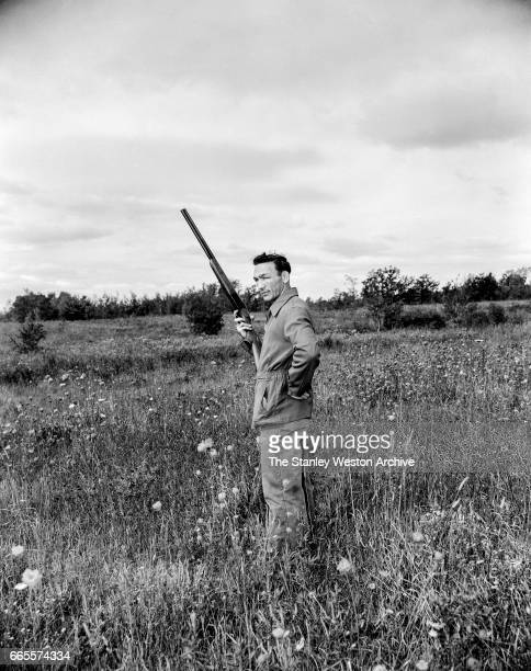 Carmen Basilio standing in a field while bird hunting in Alexandria Bay New York 1957