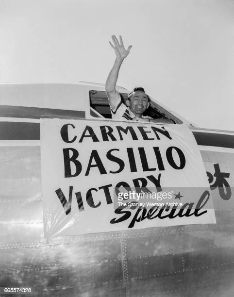 Carmen Basilio waving his hand out of the cockpit from a Mohawk Airlines airplane in Watertown New York August 20 1957