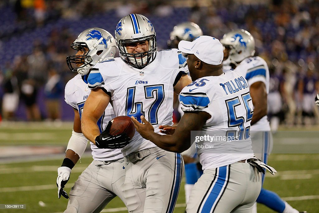 Carmen Messina #47 of the Detroit Lions celebrates with teammate Stephen Tulloch #55 after intercepting a pass against the Baltimore Ravens during the second half at M&T Bank Stadium on August 17, 2012 in Baltimore, Maryland.