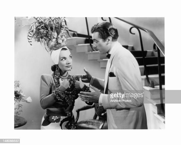 Carmen Miranda dressed ornately from head to toe as she stands with a man talking to her in a scene from the film 'WeekEnd In Havana' 1941