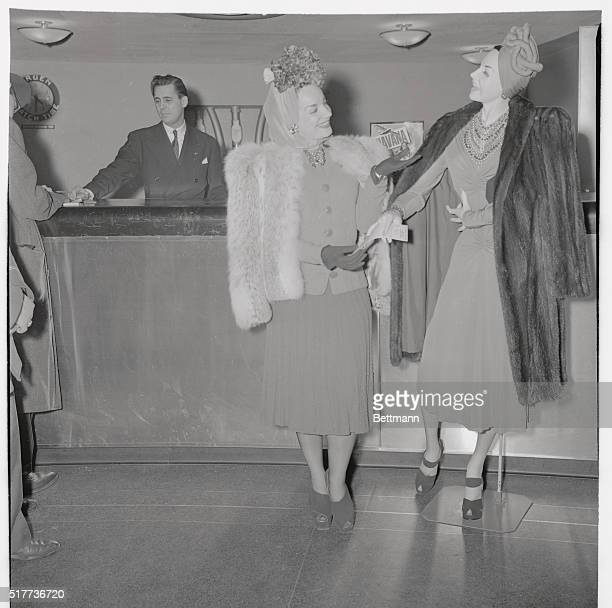 Carmen Miranda hands a lifesize manikin twin of herself a ticket to Rio de Janeiro which she had just purchased at the Pan American Airways ticket...