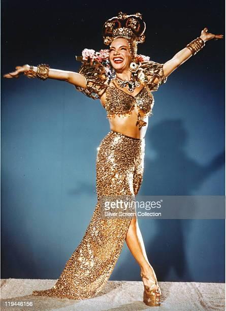 Carmen Miranda Portugueseborn Brazilian singer actress and dancer wearing a long gold sequuinned split skirt with a matching bratop and various gold...