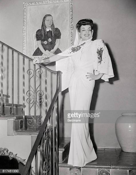 Carmen Miranda wearing flowing lines of this white crepe evening gown create the illusion of height Here again the midriff is accented by...