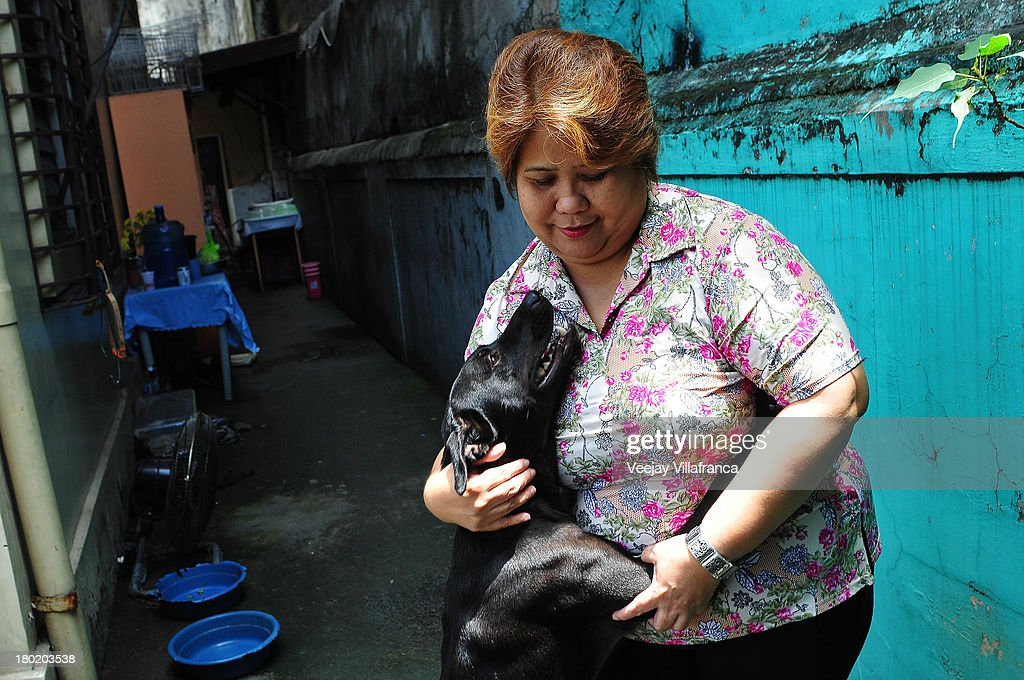 Carmencita Uy, owner of World Class Company Unlimited (WCU), plays with her dog in her compound on September 10, 2013 in Manila, Philippines. WCU is just one of dozen training centers in Manila that helps overseas contract workers with their skill requirement as they apply for domestic work abroad.