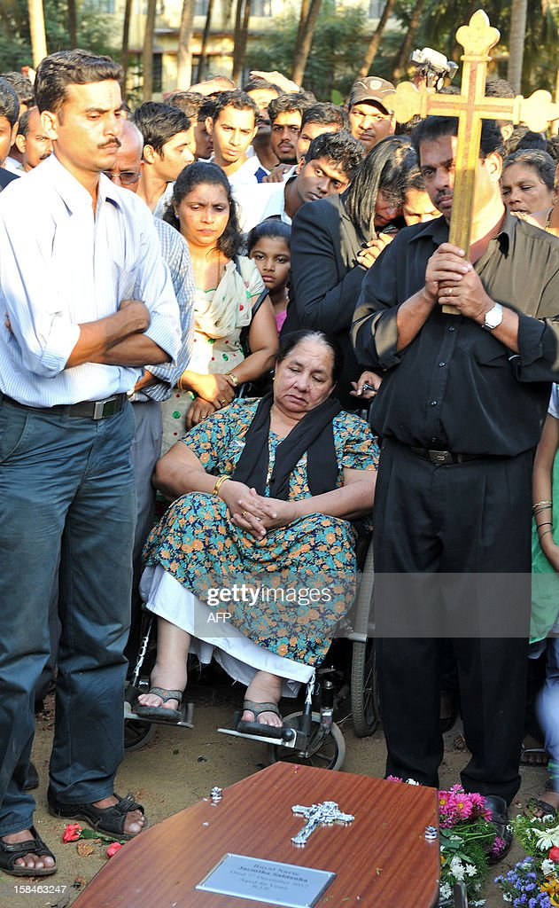 Carmine (C), on wheelchair, watches the last rites of her late daughter Jacintha Saldanha during her funeral at The Shirve Church cemetary near Mangalore on December 17, 2012. About 2,000 mourners have packed a Catholic church in southwest India for the funeral of the nurse who was found hanged after taking a hoax call to the hospital treating Prince William's wife. Indian-born Jacintha Saldanha, 46, apparently committed suicide after answering the telephone call from Australian radio DJs to the hospital where the pregnant Duchess of Cambridge was admitted with acute morning sickness. AFP PHOTO/Manjunath KIRAN