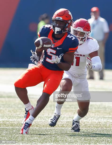 Carmoni Green of the Illinois Fighting Illini catches the ball in front of Isaiah Wharton of the Rutgers Scarlet Knights at Memorial Stadium on...