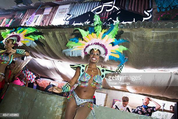 A carnival dancer performs on stage during a dj set by Basement Jaxx at the Red Bull Music Academy Sound System at Notting Hill Carnival at Notting...