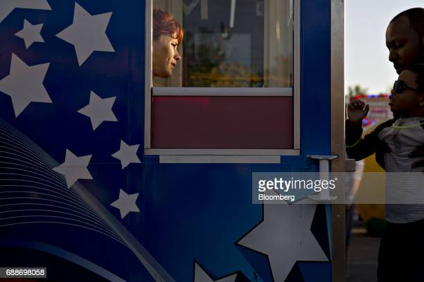 A carnival employee sits in the ticket booth during the Dreamland Amusements carnival in the parking lot of the Marley Station Mall in Glen Burnie...