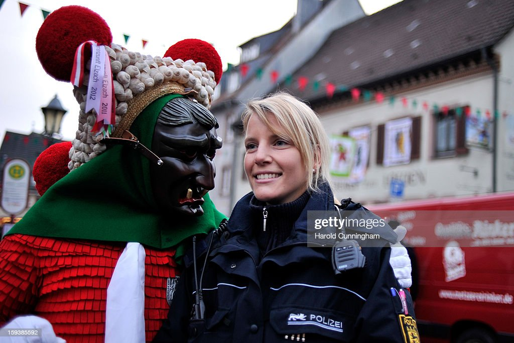 A carnival enthousiasts in a costume of the so-called 'Schuttig' hugs a police officer prior to the traditional torch parade on January 12, 2013 in Elzach, Germany. The Elzach procession launches the carnival season in southwestern Germany which culminates on Rose Monday. Dating from 1530 the carnival marks a festive period where the bad spirits are expelled prior to the Lenting season.