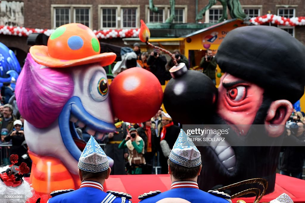 A carnival float depicting a clown facing an Islamic fighter stands in front of the city hall in Duesseldorf, western Germany, after the Rose Monday (Rosenmontag) street parade has been cancelled on February 8, 2016. Traditional Rose Monday carnival parades in several western German cities have been cancelled due to stormy weather. / AFP / PATRIK STOLLARZ