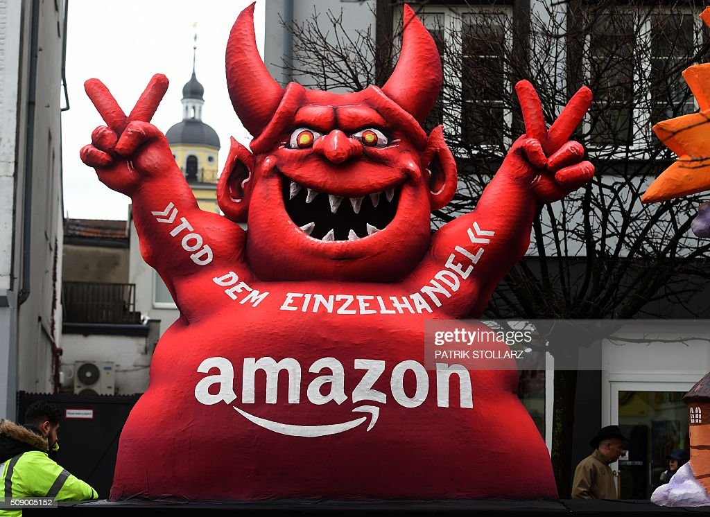 A carnival float, depicting a red devil reading 'Death of Retail - Amazon', stands in front of the city hall in Duesseldorf, western Germany, after the Rose Monday (Rosenmontag) street parade has been cancelled on February 8, 2016. Traditional Rose Monday carnival parades in several western German cities have been cancelled due to stormy weather. / AFP / PATRIK STOLLARZ