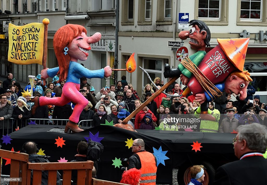 A carnival float depicting a woman lighting up a New Year's Eve rocket with two men chained on it stands in front of the city hall in Duesseldorf, western Germany, after the Rose Monday (Rosenmontag) street parade has been cancelled on February 8, 2016. Traditional Rose Monday carnival parades in several western German cities have been cancelled due to stormy weather. / AFP / PATRIK STOLLARZ